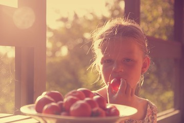 Little girl sitting on porch in summer. Tomatoes on plate. Dreamy and romantic image. Summer and happy childhood concept
