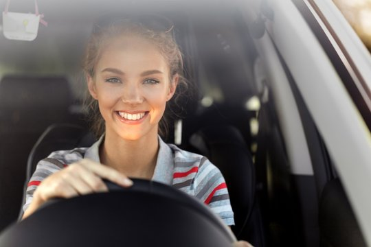Portrait of Smiling Young Woman Driving her Car