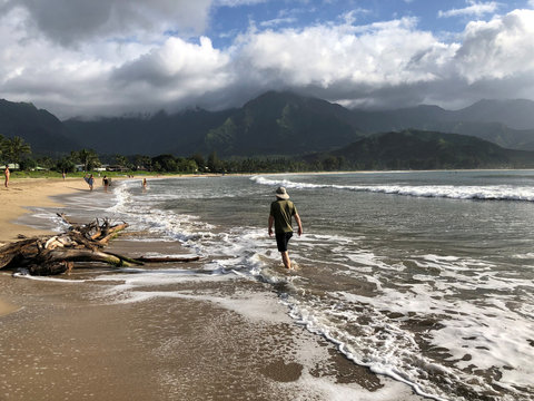 People walk along a calm Hanalei Beach as Hurricane Lane approaches Kauai Hawaii