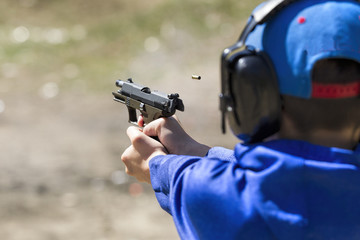 Closeup of boy shooting a pistol.