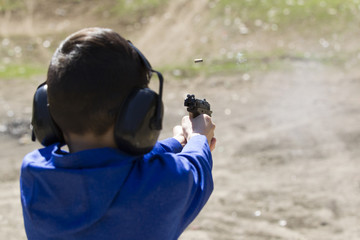 Boy does target pratice with pistol.