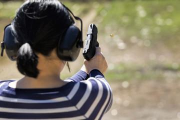 Woman shoots pistol at range.