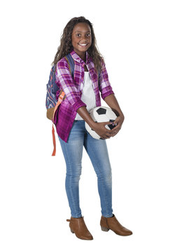 Full length portrait of a smiling African American teenage girl. Athletic female holding a soccer ball standing on a white background.