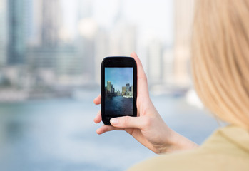 Closeup of a woman's hand taking a photo of the city on a smartphone camera.