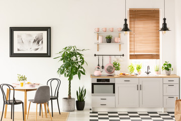 Real photo of bright kitchen interior with checkerboard floor, pastel pink accessories, fresh plants and dining table on carpet