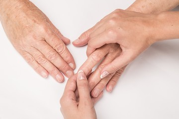 Young Woman's Hands Touching and Holding an Old Woman's Hand