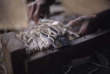 日本の伝統食品の凍みこんにゃくの製造風景、完成した凍みコンニャクのはしを切る