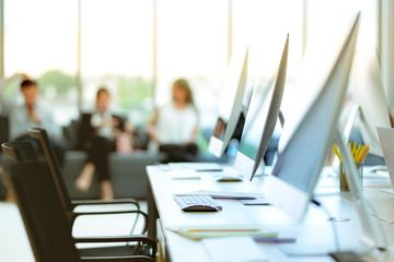 Group of business people relax  in the modern office.there are many computers on the table. .This image is blurry.