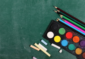 Chalks, pencils and color palette on green chalkboard, blackboard, background and texture, top view