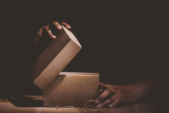 hand hold and open a mysterious box on wooden table