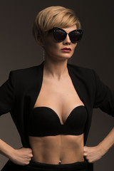 Beautiful fashion blonde woman in black glasses and black costume