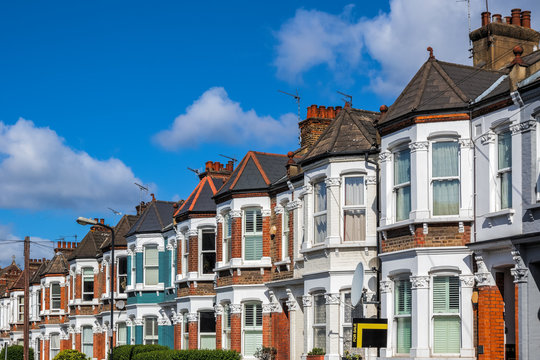 A row of typical British terraced houses in London with an estate agent sign