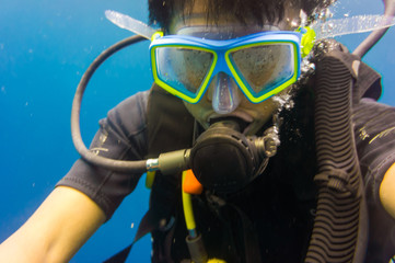 Scuba diving man with mask and underwater wetsuit take selfies photo