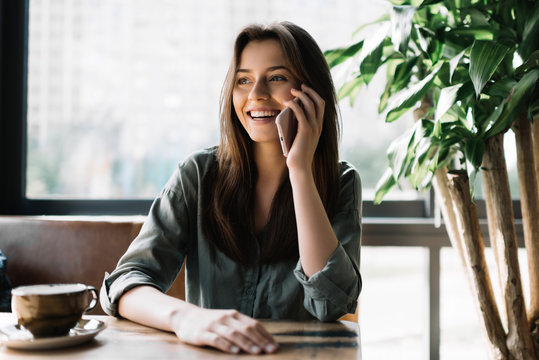 Young beautiful woman using mobile phone in modern coffee shop. Cute smiling businesswoman holding smartphone, sitting at working place.