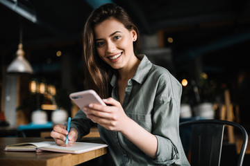 Fototapeta Cheerful female using mobile phone for online banking, shopping web, learning  language sitting in loft coffee shop.   Positive caucasian woman holding modern smartphone  and making notes to study.  obraz