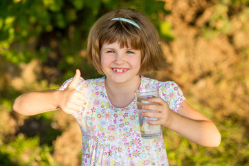 Little girl kid with glass of water in morning, drink every day. Concept of healthy habits