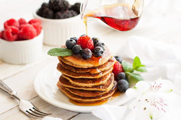 Paleo apple-cinnamon pancakes with berries, maple syrup