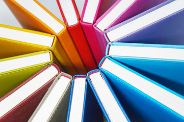 Books for colorful background. A lot of books with bright covers lined in circle. Design element, paper and leather texture, close up