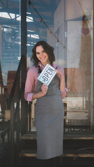 Beautiful mid 30s Caucasian female standing with an open sign near her small cafe, smiling and looking into camera. Small business concept