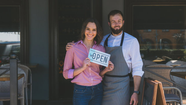 Two mid 30s Caucasian male and female business partners or couple standing with an open sign near their small cafe, smiling and looking into camera. Small business concept