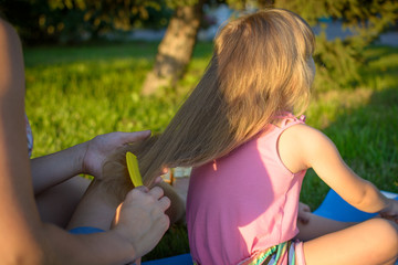 Mother comb hair of her daughter. Summer walks mom and daughter together