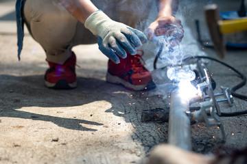 close up technician welding metal pole, dangerous worker.