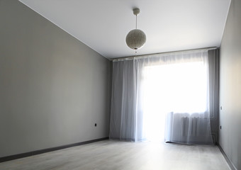 Empty room, window with white curtains