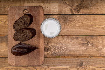 A Glass milk with bread slice on wood background