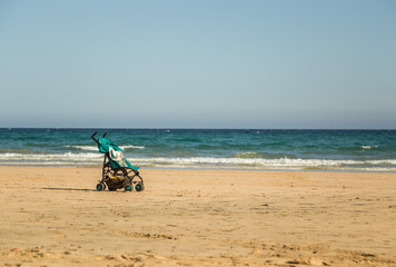 Beautiful empty sandy beach with an infant baby stroller in Fuerteventura.