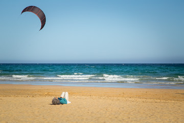 Woman lying down on sandy beach with calm water in Fuerteventura.