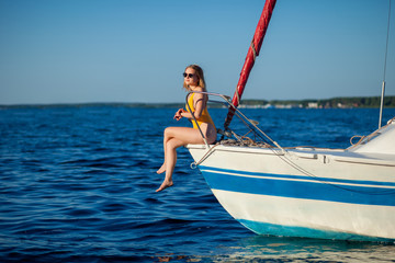 Girl sitting on the bow of the yacht, sailboat