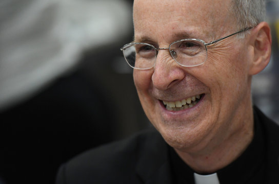 Jesuit priest father James Martin of the U.S. smiles as he signs copies of his book at the Pastoral Congress at the World Meeting of Families in Dublin, Ireland