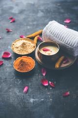 Ayurvedic face pack/mask using Gram Flour/besan, Haldi & milk ubtan placed in brass bowls with rose...