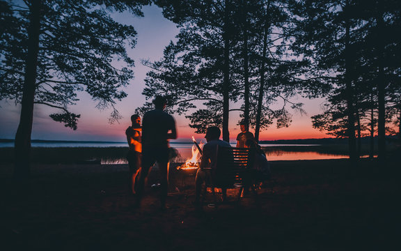 Holiday with friends in nature. Group of young people near camp fire , telling stories near the fire with wood, flames in the nature at night near lake.