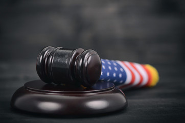Judge Gavel and United States of America flag on a black wooden background.