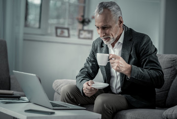 Tasty drink. Attentive bearded male having rest, drinking coffee and enjoying pause