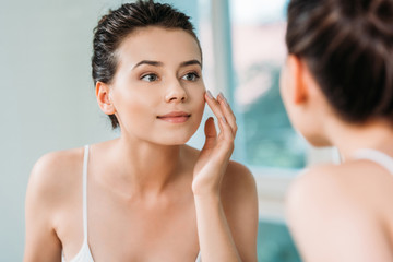 beautiful smiling young woman touching face and looking at mirror in bathroom