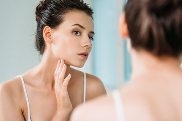 selective focus of attractive young woman touching face and looking at mirror