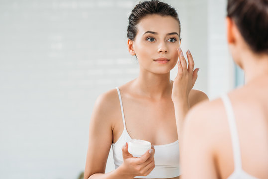 beautiful girl applying face cream and looking at mirror in bathroom