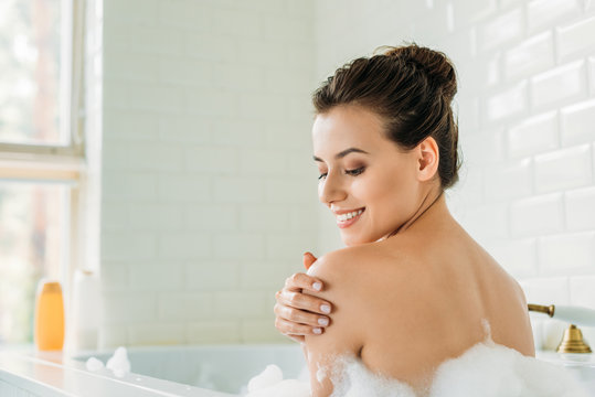 beautiful smiling young woman relaxing in bathtub with foam