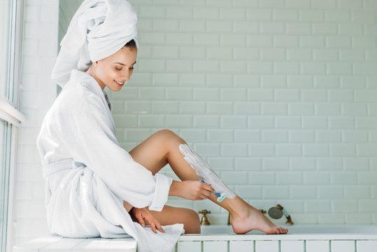 beautiful smiling young woman shaving leg with razor in bathroom