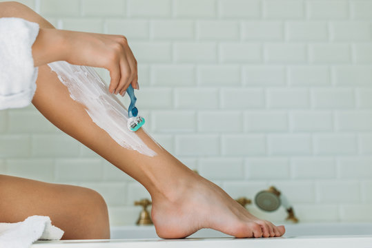cropped shot of young woman shaving leg with razor in bathroom
