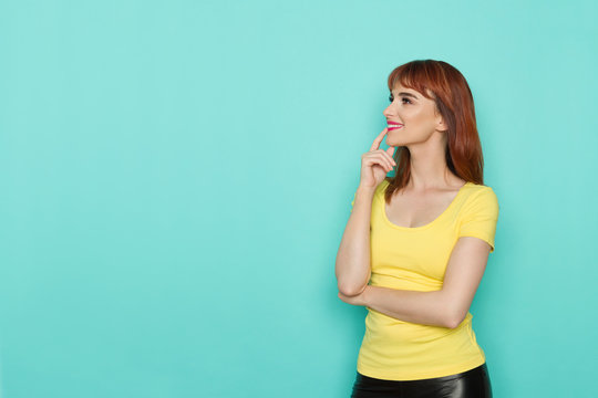 Curious Young Woman In Yellow Shirt Is Looking Away And Smiling