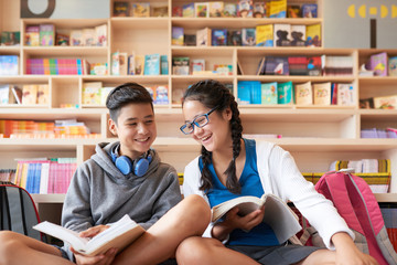 Teenage boy and girl sitting in library holding books and smiling on bookshelves background