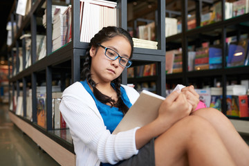 Diligent schoolgirl in glasses sitting near bookshelf in library of school and reading book alone