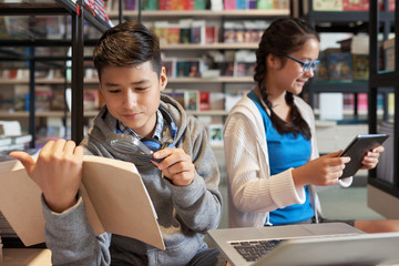 Curious boy exploring book with magnifier and girl using tablet while sitting in school library