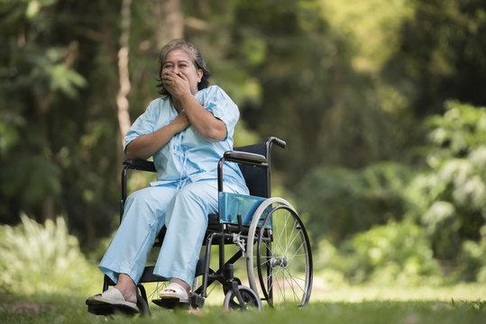 Lonely elderly woman sitting sad feeling on wheelchair at garden in hospital