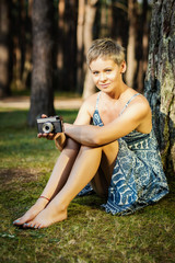portrait of a beautiful woman with a camera in hand posing in a summer forest