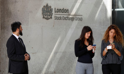 People check their mobile phones as they stand outside the entrance of the London Stock Exchange in London