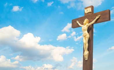wood crucifix the body of Christ on the cross on the blue sky cloudy with copyspace